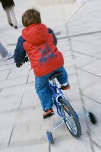 A boy rides a bicycle on a paved footpath. Training wheels are attached to the bike.