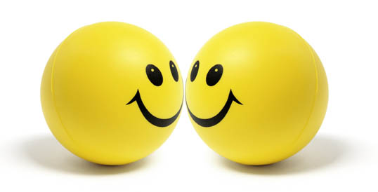 Photo of two yellow spheres with large smiley faces on them.