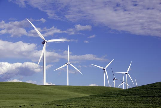 A photo of a green, slightly hilly landscape with a handful of wind turbines in the background.