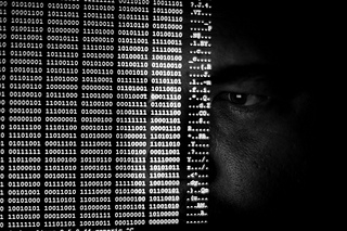 A man's face obscurred by a flow of binary numbers.