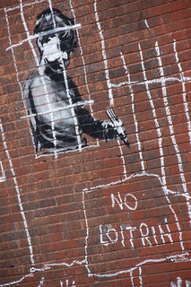 Stencil art on a wall showing a boy scrawling 'No loitrin'