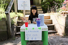 A girl promotes her lemonade stand with handwritten signs.