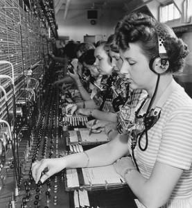 A line of 1940's era telephone exchange operators listening to callers.