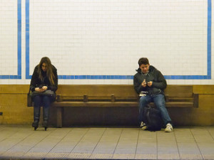 Strangers on a station engrossed in their phone screens.