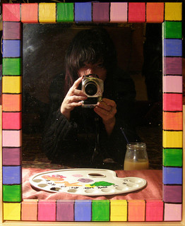 A man in a colored frame with a paint palette and a camera