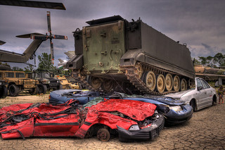 Cars getting compressed by a tank