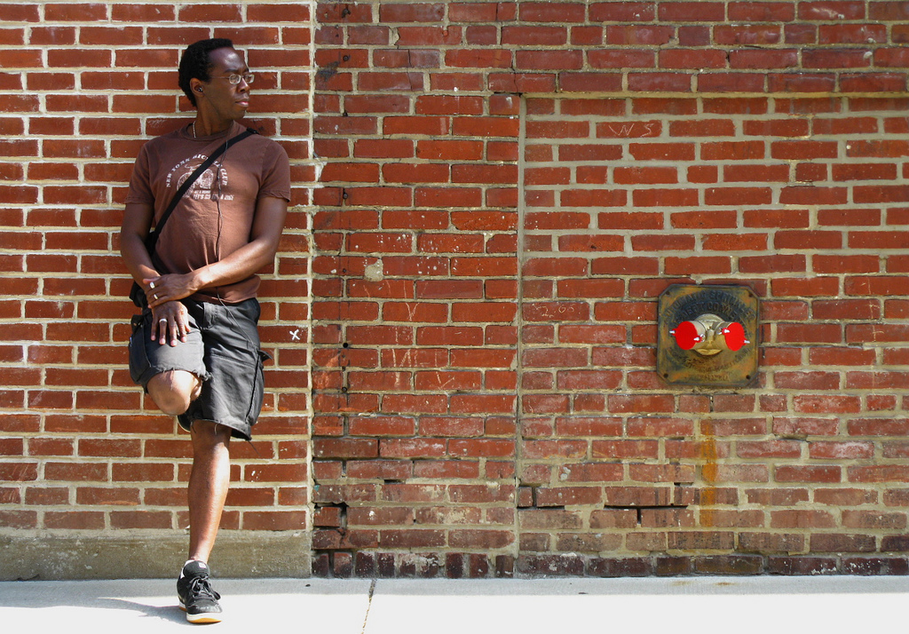Man posing against a brick wall