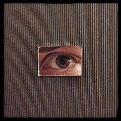 An eye looking through a tiny window