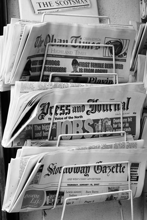 3 folded newspapers on a newsstand.