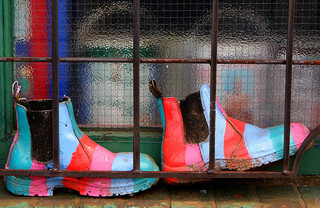 Colorful boots behind a cage door