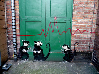 Banksy graffiti rats with a graph axis across a green door