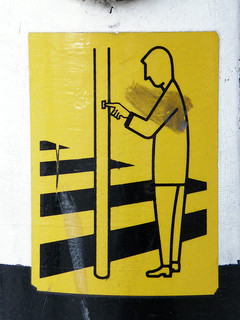 Sign showing a person pressing a button