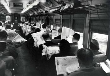 A commuter train full of passengers engrossed in their newspapers.