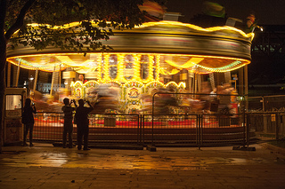Night time: Fairground carousel speeds around as passers-by watch.