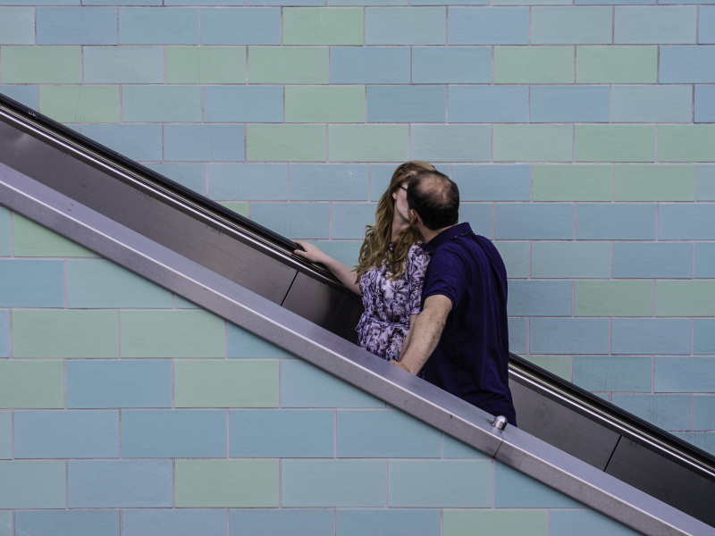 A couple kissing on an escalator - before
