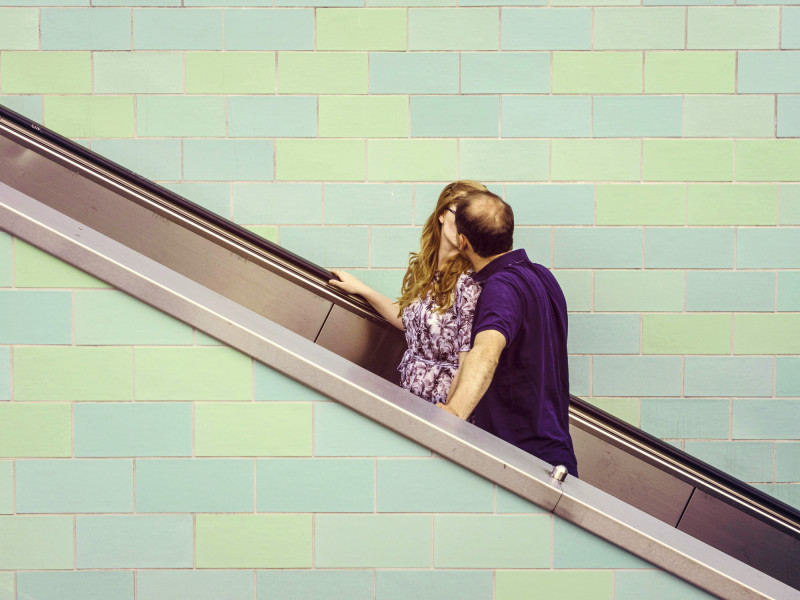 A couple kissing on an escalator - after