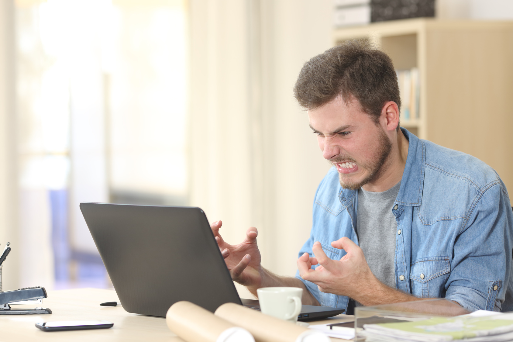 Stock photo of man angry at computer