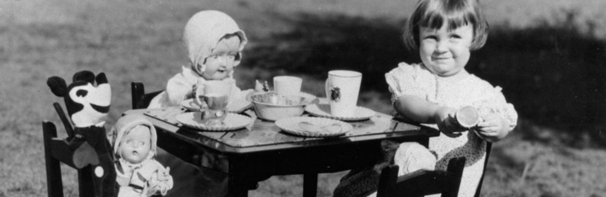 Young girl entertaining Mickey Mouse and other friends at a make-believe tea party, 1930s