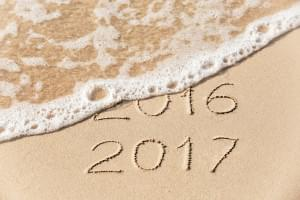2016 2017 inscription written in the wet yellow beach sand being washed with sea water wave